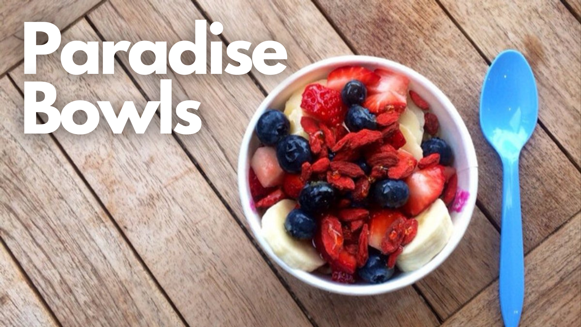 Paradise Bowls, Manhattan Beach, California, picture of an acai bowl with some strawberries blueberries and raspberries and bannana in a bowl with a blue sppon to the right of the bowl and some text to the left of the bowl