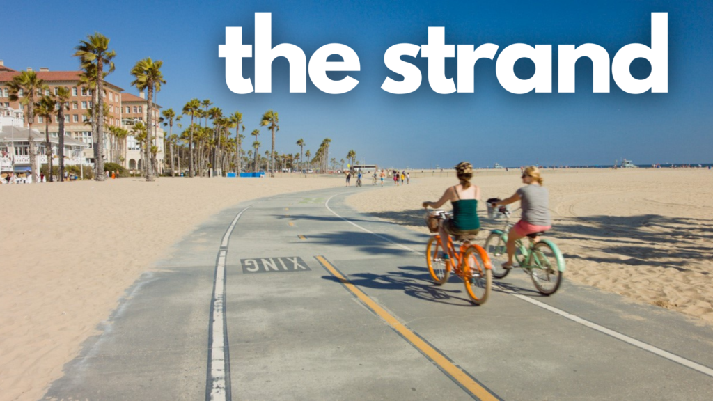 The Strand Bike Path - Santa Monica to Redondo Beach with two bikers on the path one that's orange and one that's green next to the beach with sand on both sides of the bike path